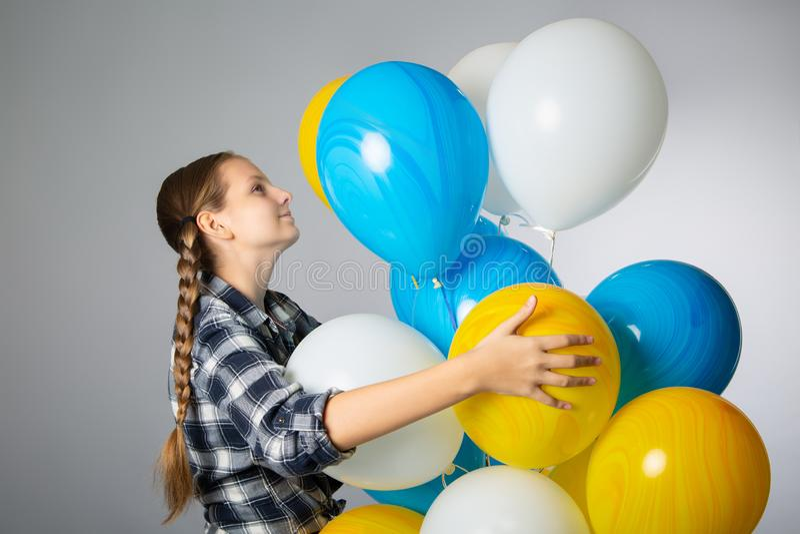 Gullig tonårig flicka som rymmer en grupp av färgrika ballonger arkivfoton