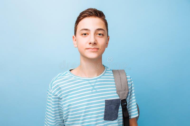 Gullig tonåring med en portfölj, på en blå bakgrund arkivfoton