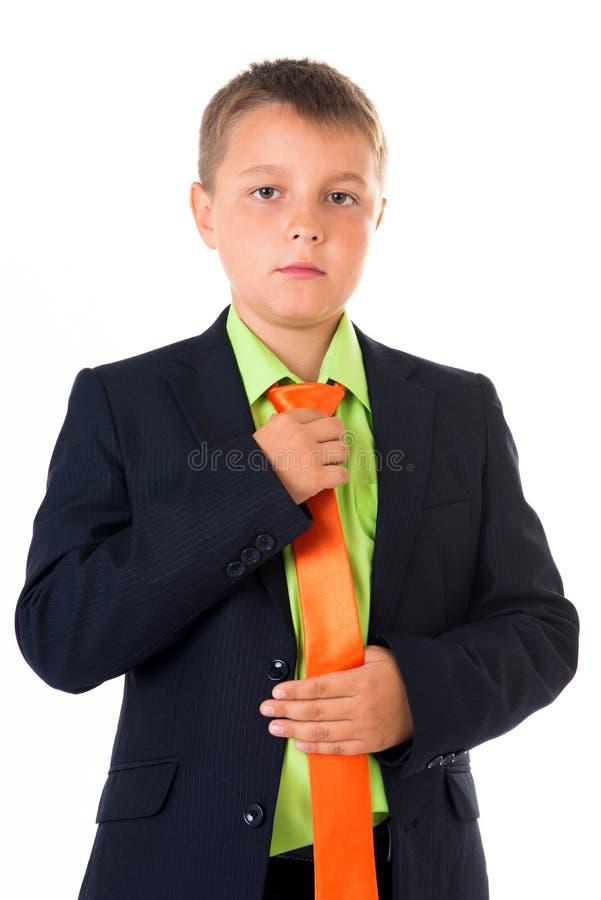 Gullig tonåringpojke i den tillbaka affärsdräkten som korrigerar bandet över vit isolerad bakgrund, halv kropp, framtida karriärb arkivfoto