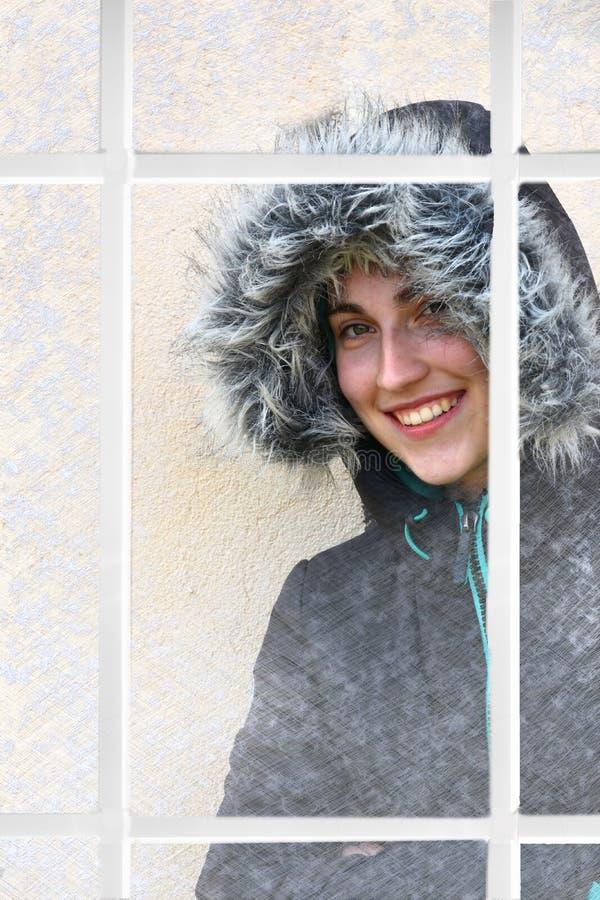 Gullig tonårs- flicka bak ett fönster med djupfrysta smattrande royaltyfri bild