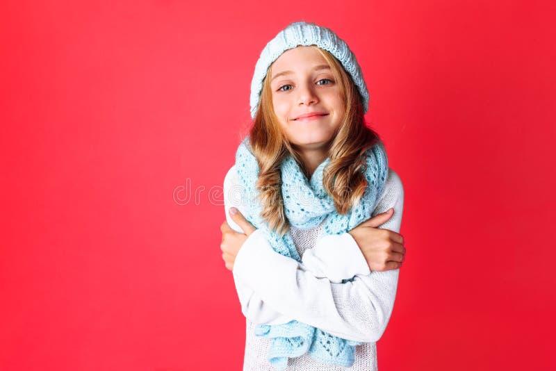 Gullig tonårs- flicka i det vita tröjaanseendet som isoleras på rosa bakgrund som bär den varma blåa hatten och den varma halsduk fotografering för bildbyråer