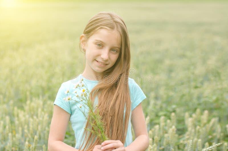 Gullig tonårs- flicka med charmiga leendeplockningtusenskönor arkivbild