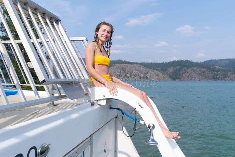 Gullig tonårs- flicka på en vattenglidbana på en sjö fotografering för bildbyråer