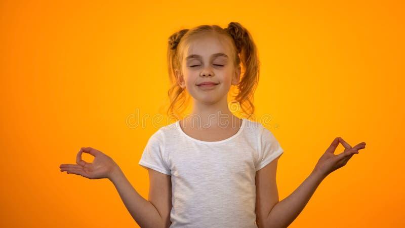 Gullig tonårs- flicka som mediterar, övande yoga efter den emotionella dagen, avkoppling royaltyfria foton