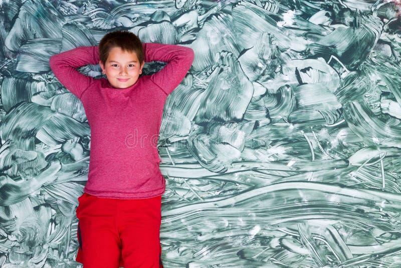 Gullig tweenpojke som kopplar av på stor grön målning arkivbilder