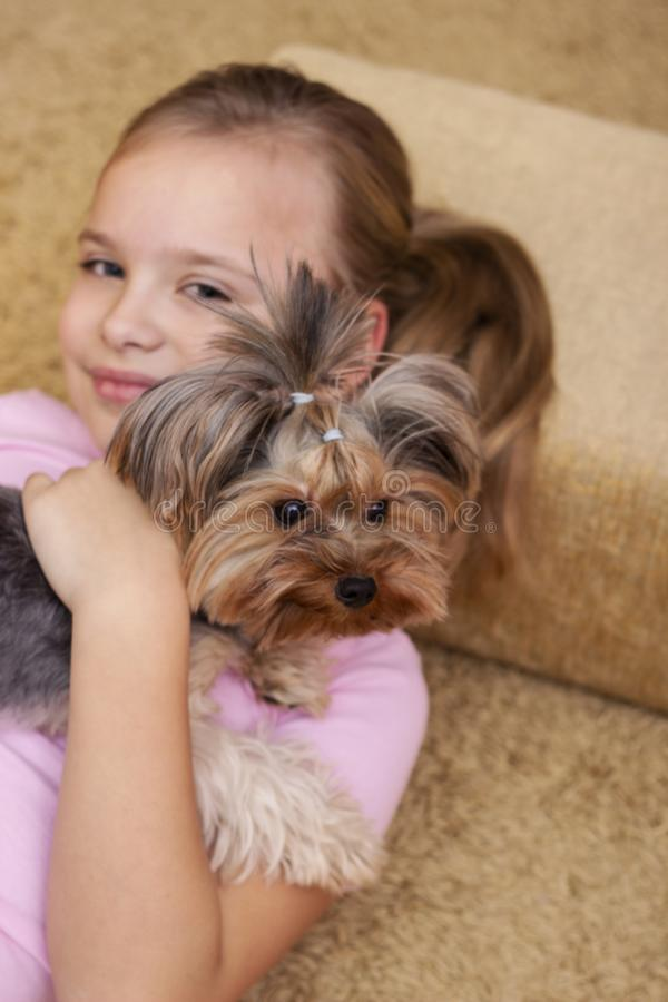Gullig ung blond flicka med hennes valp för Yorkshire terrier som ligger på soffan royaltyfri bild