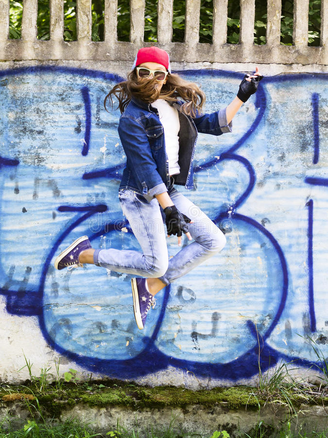 Gullig ung blond tonåringflicka i en baseballmössa- och jeansskjortabanhoppning mot en bakgrund för stenvägg Höftflygtur, royaltyfria bilder