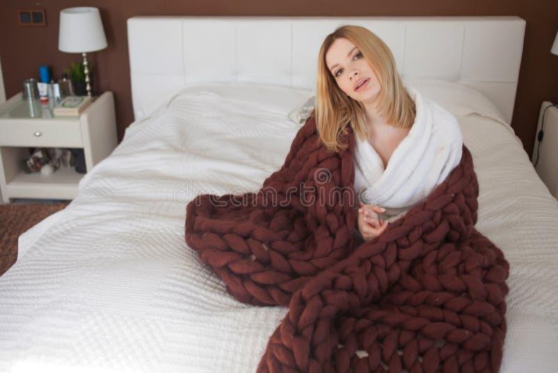 Gullig ung blondin hemma i sovrummet som sitter p? s?ngen som sl?s in i en stor brun filt arkivbild