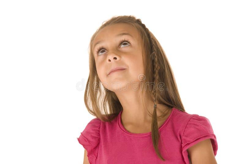 Gullig ung brunettflicka som lägger på hennes händer som ser upp royaltyfria foton