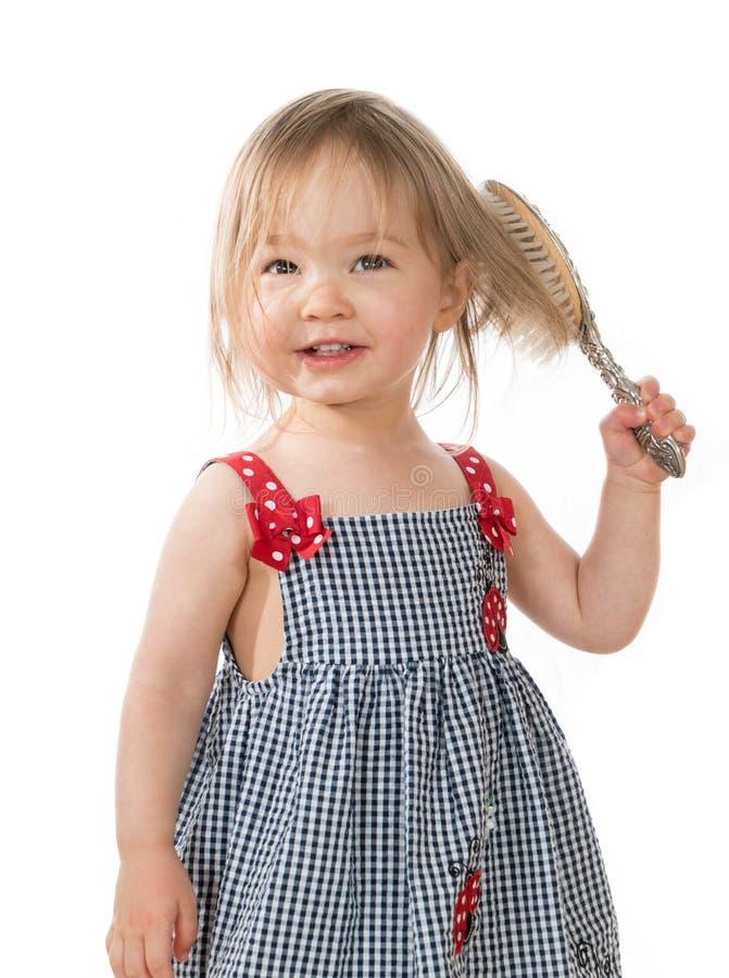 Gullig ung caucasian flicka som borstar hår med den gamla hårborsten arkivbilder