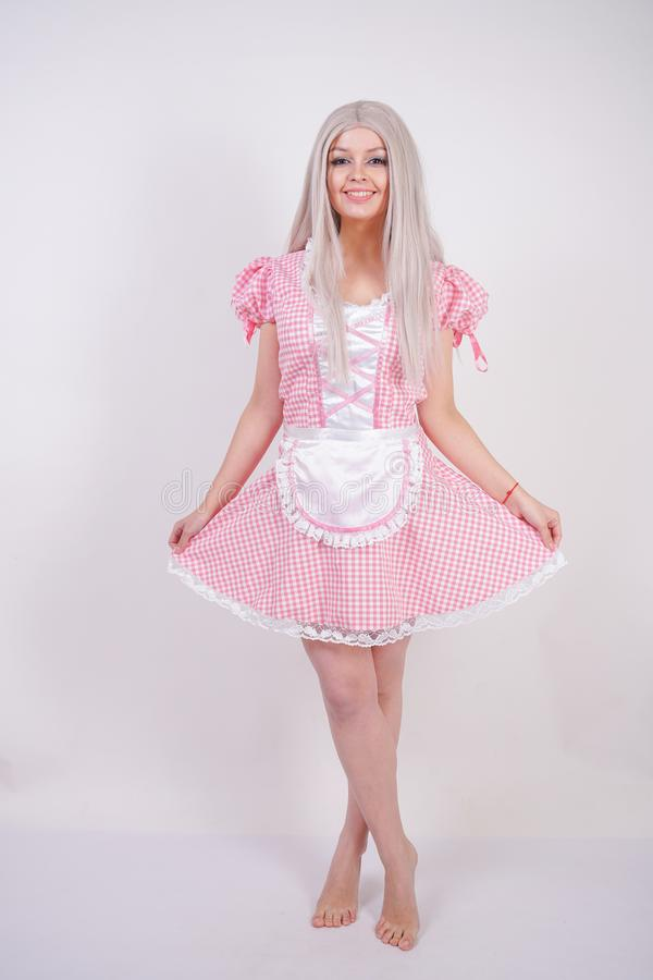 Gullig ung caucasian tonårig flicka i bayersk klänning för rosa pläd med förklädet som poserar på fast bakgrund för vit studio royaltyfria foton