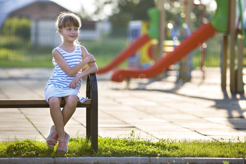 Gullig ung flicka i den korta klänningen som bara utomhus sitter på lekplatsbänk på solig sommardag royaltyfri foto