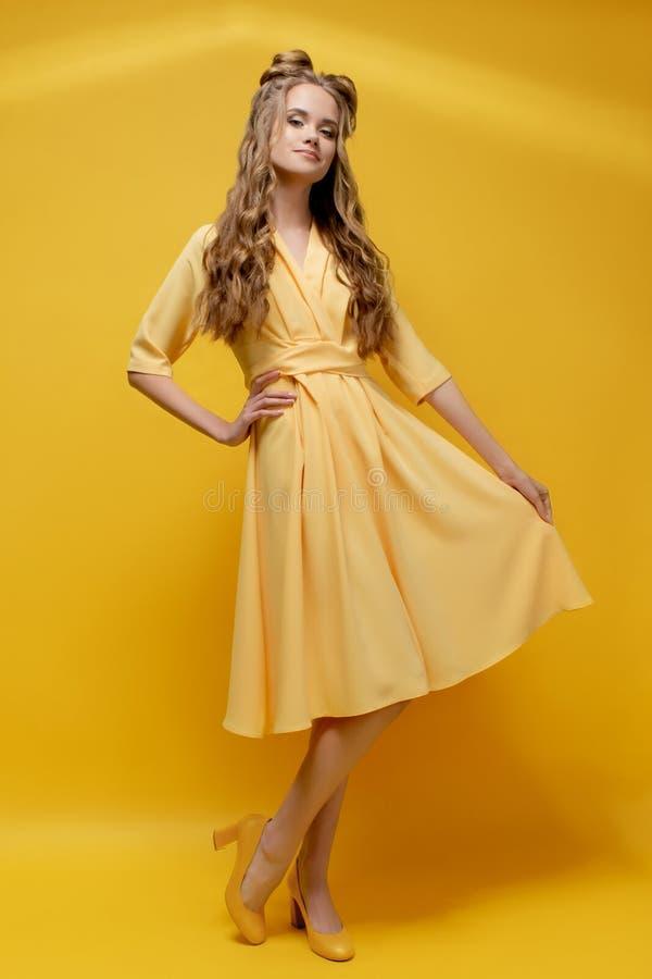 Gullig ung flicka i en gul klänning på en gul bakgrund med en frisyr och ett lockigt långt hår arkivbild