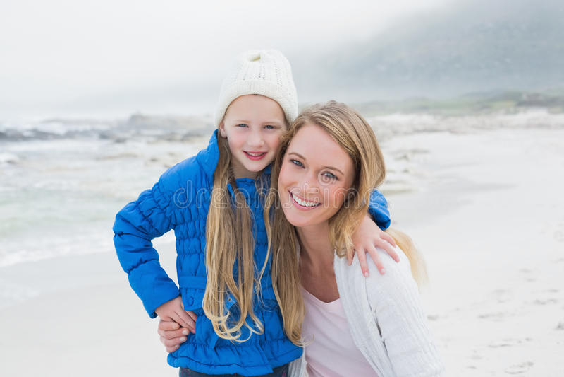 Gullig ung flicka med att le modern på stranden arkivbilder