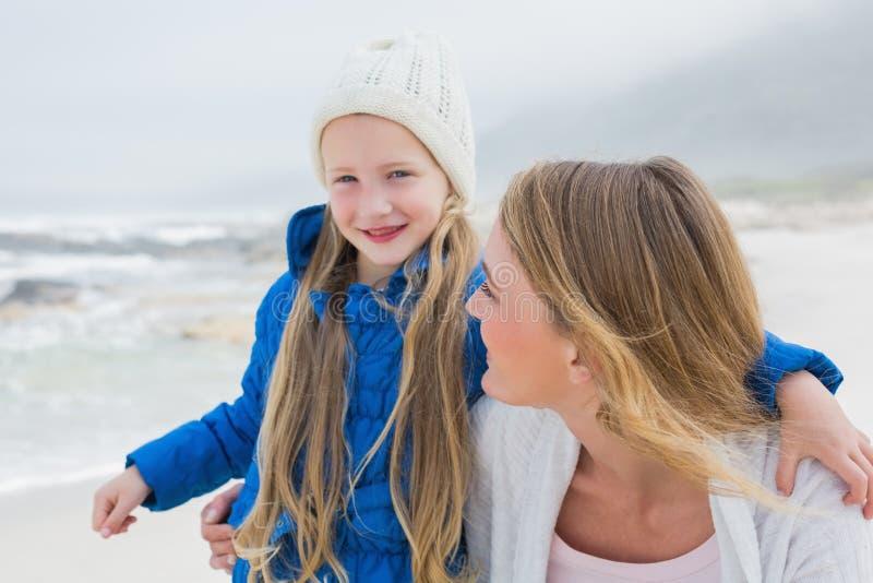 Gullig ung flicka med att le modern på stranden arkivbild