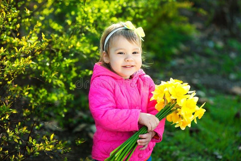 Gullig ung flicka med en bukett av gula påskliljor i vårträdgård arkivfoto