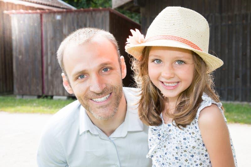 Gullig ung flicka med familjen för man för stilig fader för sugrörhatt den enkla royaltyfria bilder