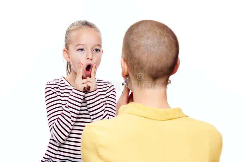 Gullig ung flicka med logopeden som öva korrekt uttal Begrepp för barnanförandeterapi på vit bakgrund arkivfoto