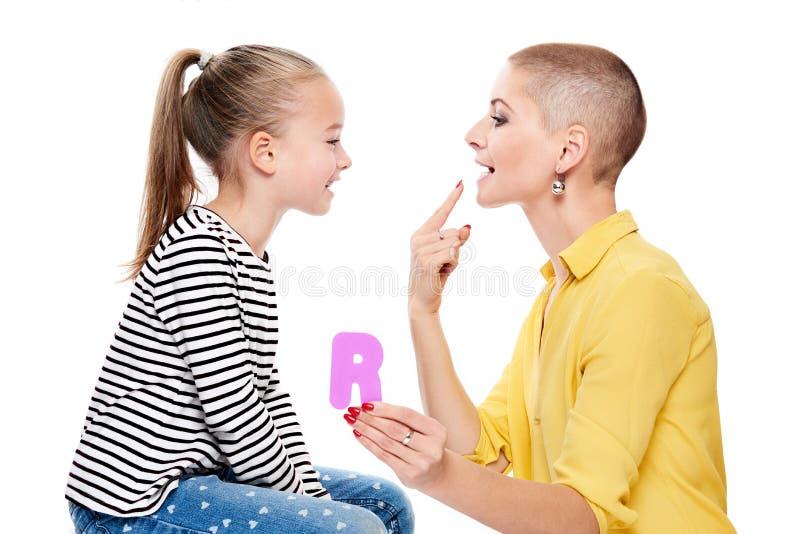Gullig ung flicka med logopeden som öva korrekt uttal Begrepp för barnanförandeterapi på vit bakgrund royaltyfri bild
