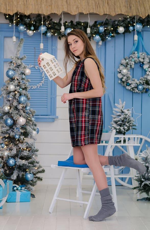 Gullig ung flicka nära julträdet med en gåva i henne händer arkivbilder