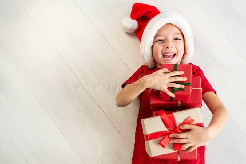 Gullig ung flicka som bär den santa hatten som ligger på golvet, rymmer julgåvor och skrattar på kameran Lycklig unge på jul fotografering för bildbyråer