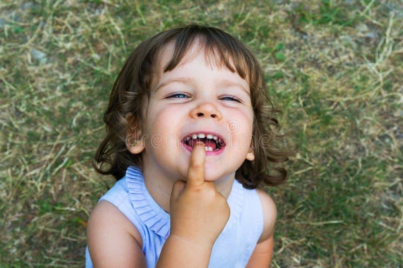 Gullig ung flicka som grinar och är enfaldig arkivfoton
