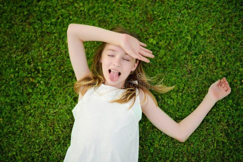Gullig ung flicka som har gyckel på ett gräs på trädgården på solig sommarafton fotografering för bildbyråer