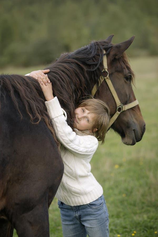 Gullig ung flicka som kramar härlig horse& x27; s-hals och se kameran Livsstilstående royaltyfria foton