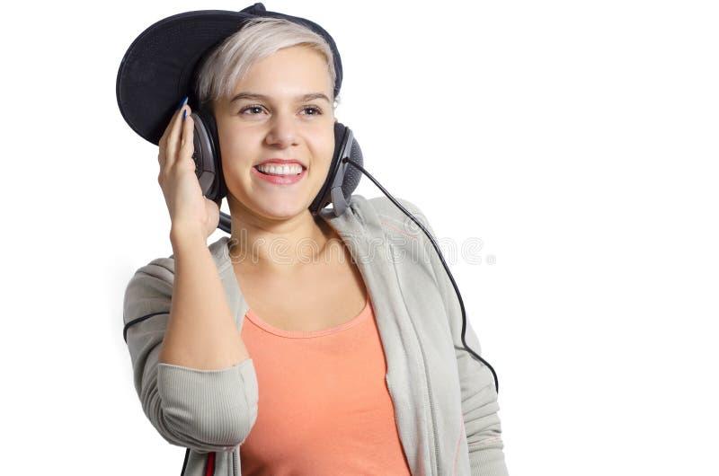 Gullig ung flicka som lyssnar till musik på hörlurar royaltyfri foto