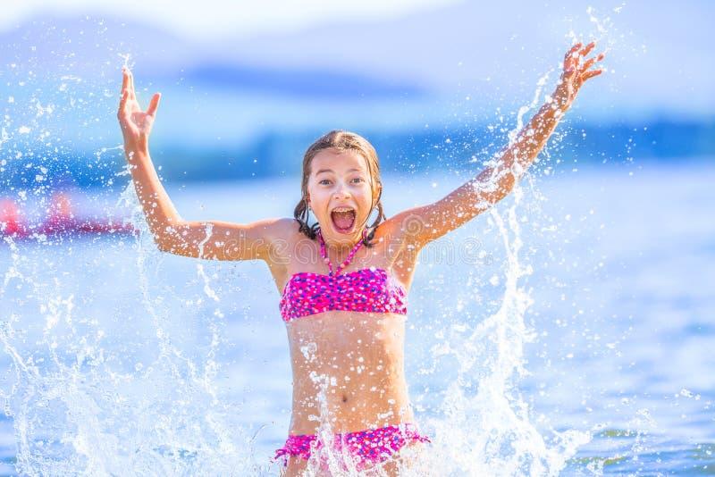 Gullig ung flicka som spelar i havet Den lyckliga pre-tonåriga flickan tycker om sommarvatten och semestrar i feriedestinationer royaltyfria foton