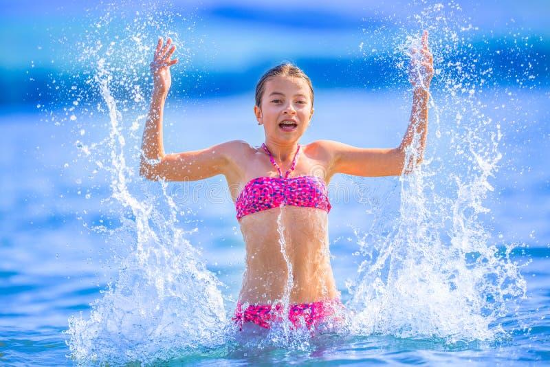 Gullig ung flicka som spelar i havet Den lyckliga pre-tonåriga flickan tycker om sommarvatten och semestrar i feriedestinationer arkivbild
