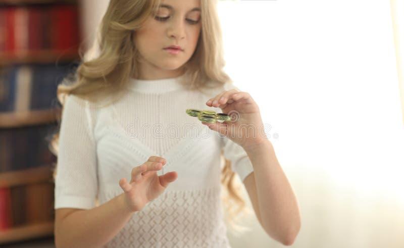 Gullig ung flicka som spelar med den gröna rastlös människaspinnaren royaltyfri foto