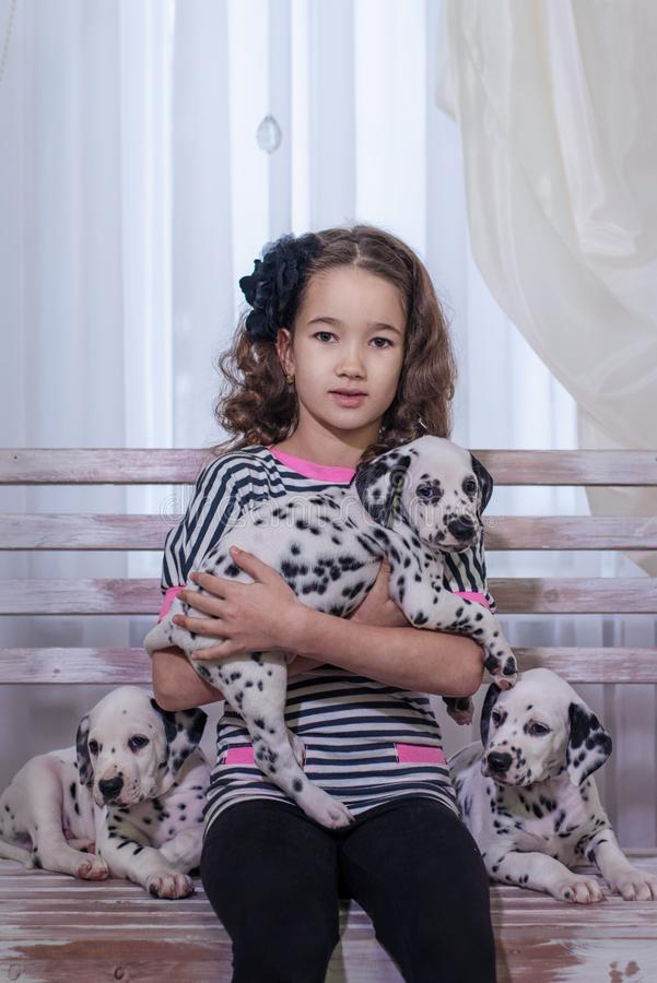 Gullig ung flicka som spelar med valpar av dalmatianen inomhus Hon är rädd arkivfoto
