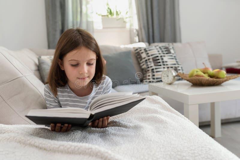 Gullig ung flickaläsebok hemma royaltyfria bilder