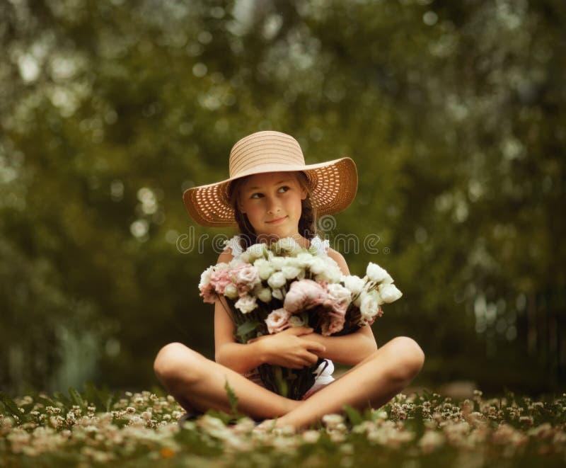 Gullig ung härlig flicka med två flätade trådar som rymmer den stora buketten av pionblommor Sommartid arkivbild