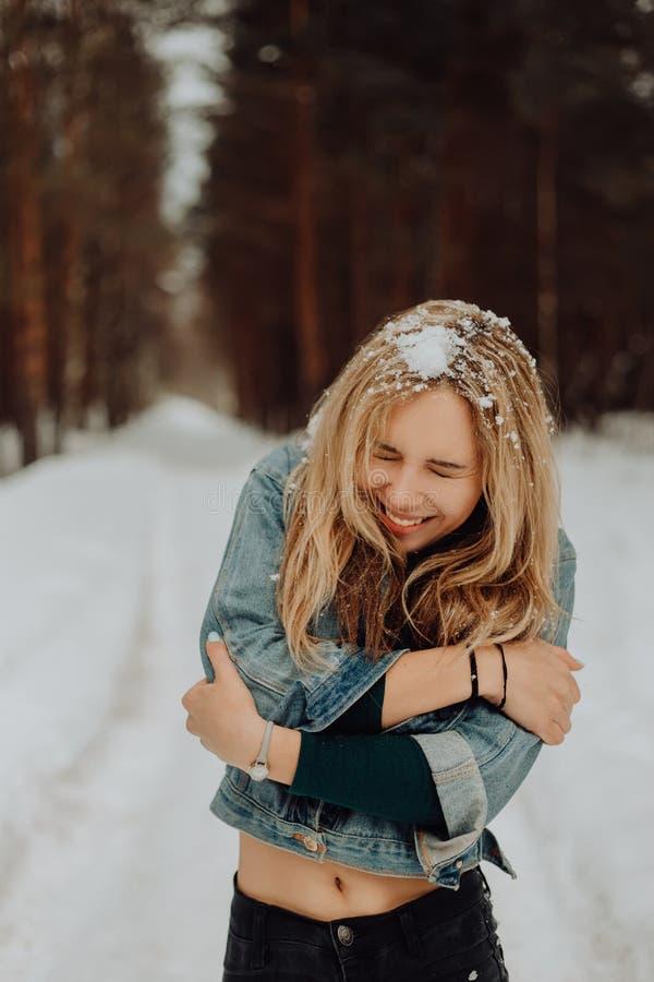 Gullig ung härlig le flickastående i snöig skog för vinter med snö på hans hår royaltyfri foto