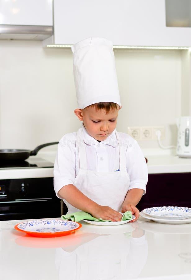 Gullig ung kock som kontrollerar hans matställeplattor arkivbilder