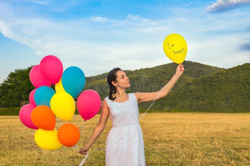 Gullig ung kvinna i den vita klänningen med ballonger i hennes händer Begreppet av frihet och glädje Ballong med text i den vänst royaltyfri fotografi