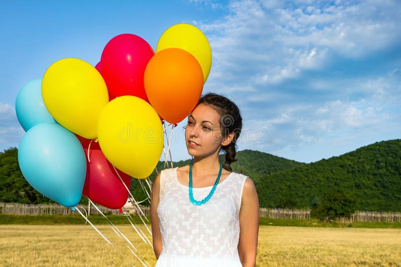 Gullig ung kvinna i den vita klänningen med ballonger i hennes händer Begreppet av frihet och glädje close upp royaltyfria bilder
