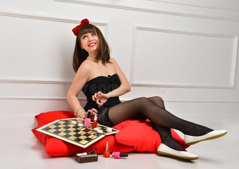 Gullig ung kvinna i en svart kl?nning och strumpor sitter på röd kudde och förbereder sig för ett datum Hon anv?nder sk?nhetsmede royaltyfri fotografi