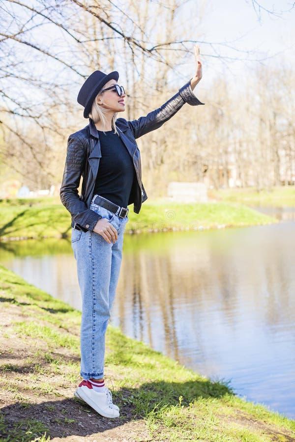 Gullig ung kvinna i grov bomullstvill, svart omslag och hatt utomhus arkivbilder