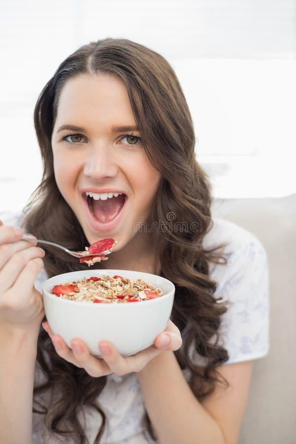 Gullig ung kvinna i pyjamas som äter frukt- sädesslag arkivfoton