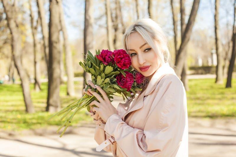 Gullig ung kvinna med blommor utomhus fotografering för bildbyråer