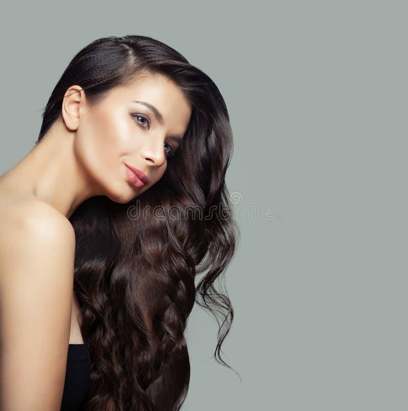 Gullig ung kvinna med långt lockigt hår, makeup och klar hud, modestående arkivfoto