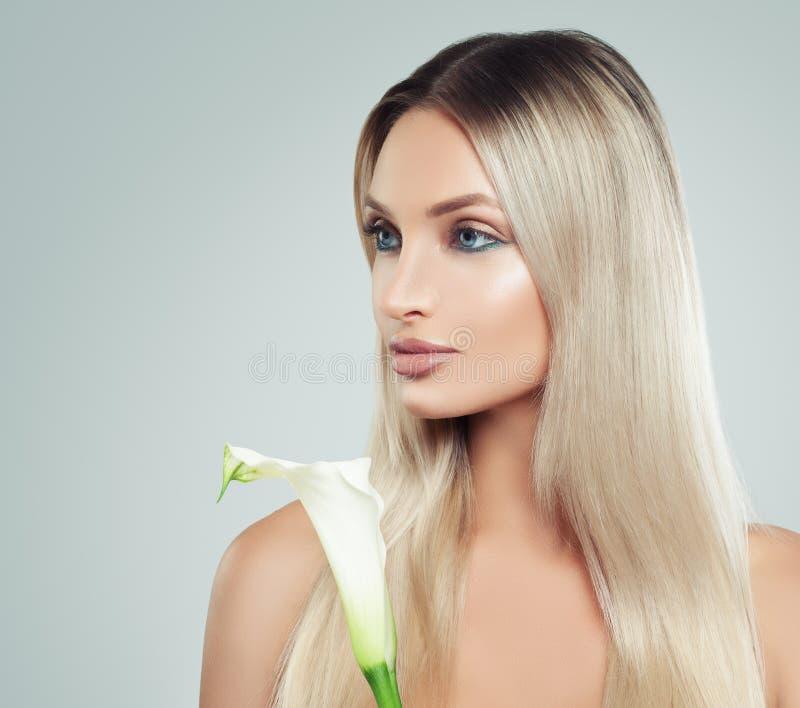 Gullig ung kvinna med ny hud, sunt hår och Lily Flowers royaltyfri bild
