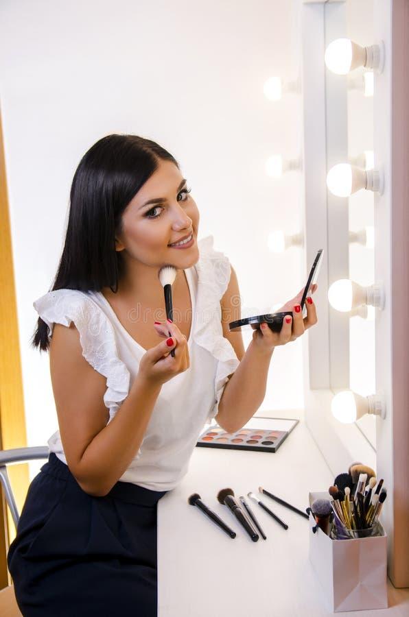 Gullig ung kvinna som applicerar makeup arkivfoton