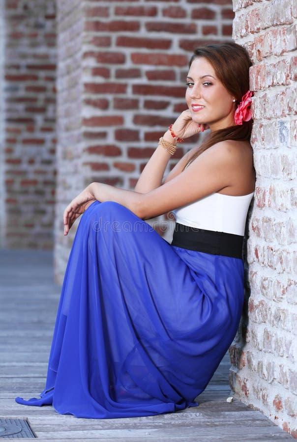 Gullig ung kvinna som plattforer nära en vägg arkivfoton