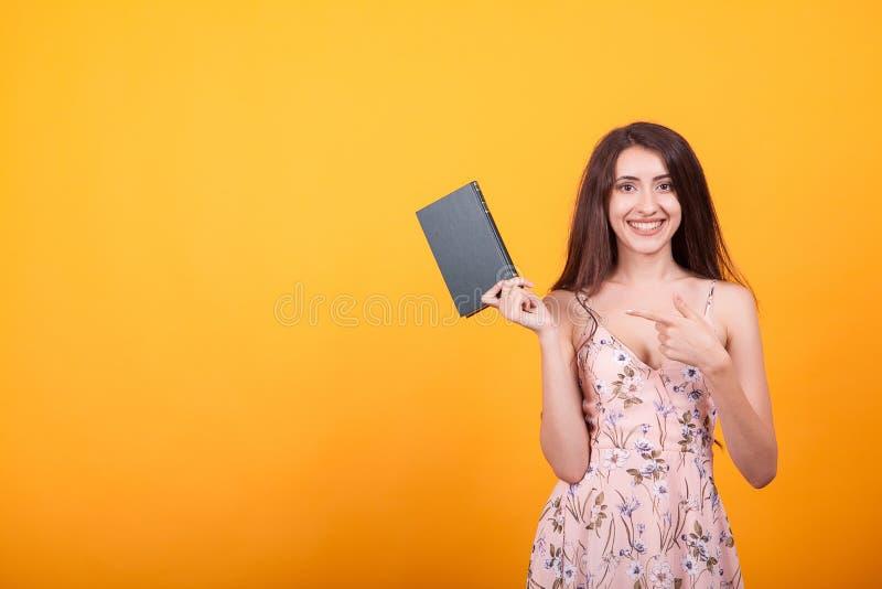 Gullig ung kvinna som rymmer en röd bok i studio över gul bakgrund arkivbilder