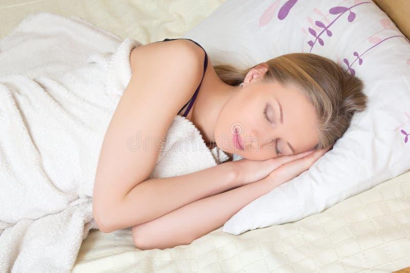 Gullig ung kvinna som sover på säng royaltyfri fotografi