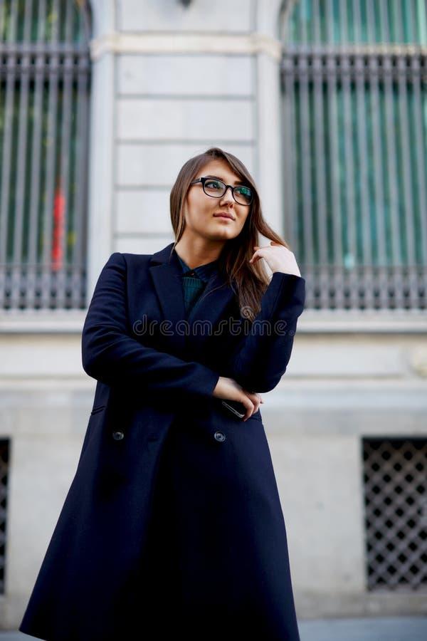 Gullig ung kvinnlig som ler och står på en gata royaltyfria bilder